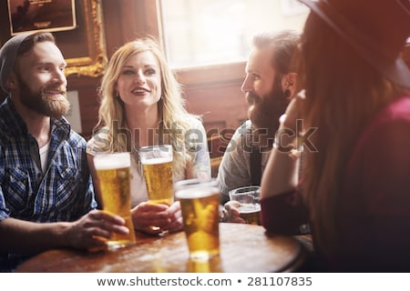 Men and women at the counter of a bar enjoying their drinks Stock photo © Kzenon