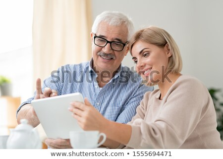 Senior grey-haired man and his pretty daughter watching online video in tablet Stock photo © pressmaster