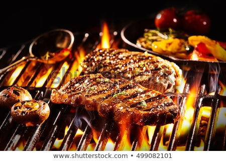 Pieces of meat on grill over fire Stock photo © dashapetrenko
