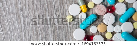 Banner of A lot of colorful medication and pills from above on grey wooden background. Stock photo © Illia