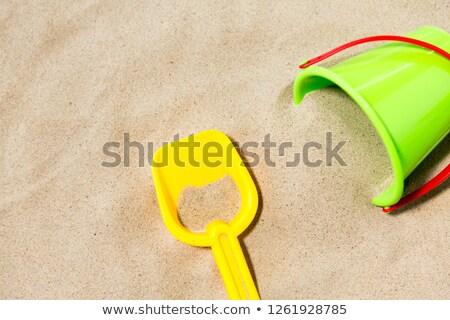 Közelkép vödör gereblye tengerparti homok játékok gyermekkor Stock fotó © dolgachov