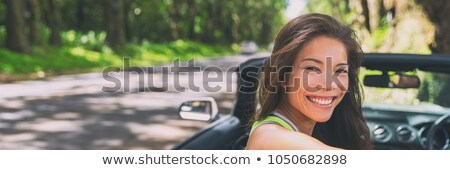 Happy young Asian woman relaxing in convertible car on summer road trip vacation. Travel destination Stock photo © Maridav