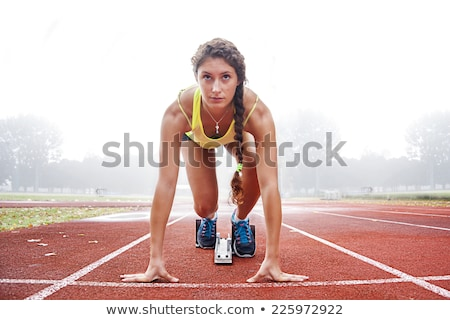 Young female athlete on athletics running track Stock photo © darrinhenry