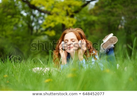 Woman lying in field listening to music Stock photo © photography33