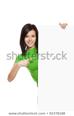 Attractive smiling woman holding white empty paper and pointing on it isolated on white stock photo © artjazz