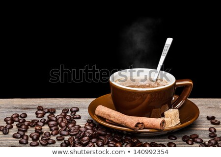 A cup of coffee, and cinnamon, coffee beans around it. Stock photo © justinb