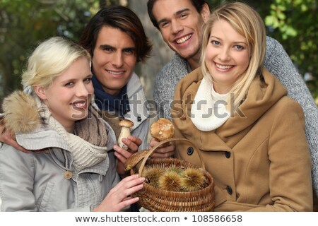 group of young people with a basket of chestnuts and mushrooms stock photo © photography33