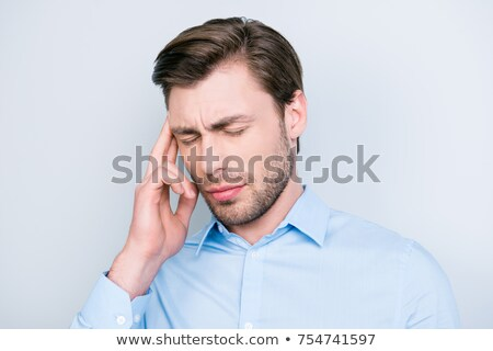 Close-up of a businessman with a migraine holding his temples. Stock photo © dacasdo