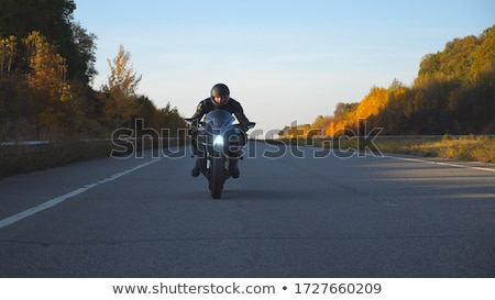 Motorcyclist in action in sunset light Stock photo © Anna_Om