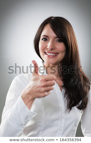 Pretty lively brunette giving a thumbs up gesture Stock photo © stryjek