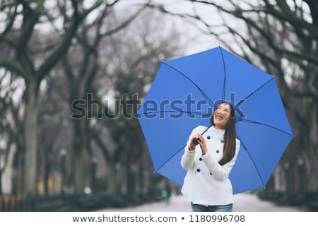 Woman with umbrella enjoy snowfall on street Stock photo © vetdoctor