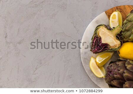 Two Artichokes With Lemon on Wooden Plate Stock photo © tobkatrina