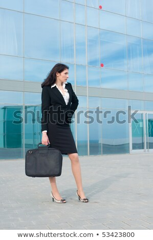 Happy young black business woman standing holding laptop bag stock photo © darrinhenry