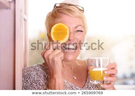 Vivacious playful woman with fresh orange slices Stock photo © dash