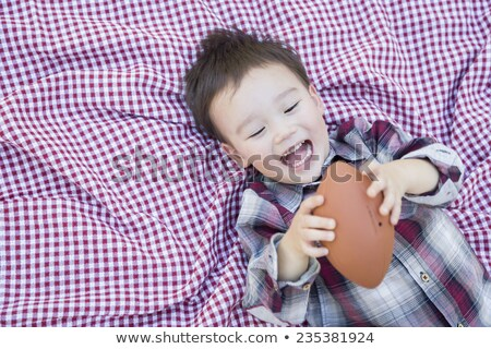 Young Mixed Race Boy Playing with Football on Picnic Blanket Stock photo © feverpitch