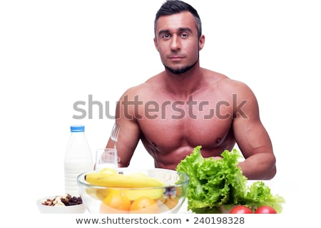 serious muscular man sitting at the table with sports nutrition stock photo © deandrobot