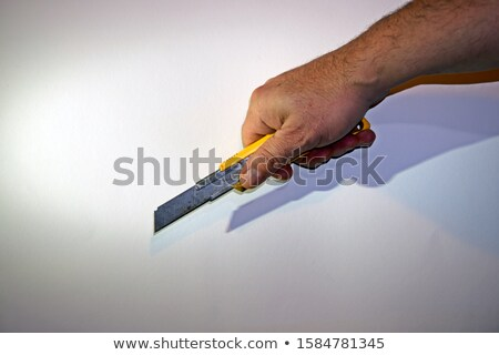 Hand holding a box cutter Stock photo © tangducminh