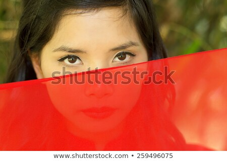 vietnamese woman peeking over red fabric Stock photo © smithore