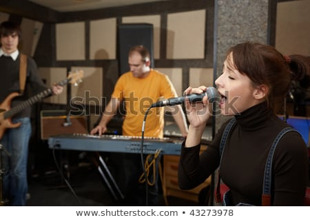 Stock photo: Vocalist girl is singing in studio. keyboard player in out of focus