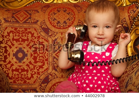 Little girl in red dress talking vintage phone. Interior in retro style. Horizontal format. Close up Stock photo © Paha_L