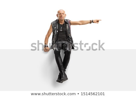 rocker girl in leather side posing seated in studio Stock photo © feedough