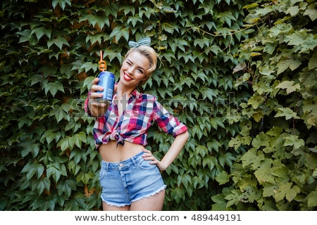 Stock photo: Young pin up girl holding glass bottle and winking