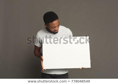 fiatalember · tart · lap · papír · mosolyog · izolált - stock fotó © nyul
