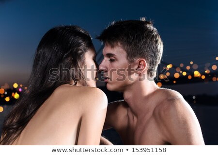 Cheerful young couple hugging on the beach at night Stock photo © deandrobot