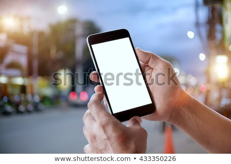 businessman texting with mobile phone on the street at night stock photo © stevanovicigor