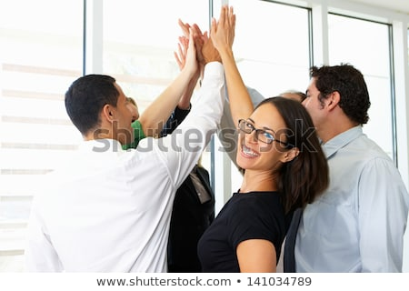 Portrait of a smiling woman giving high five to camera Stock photo © deandrobot