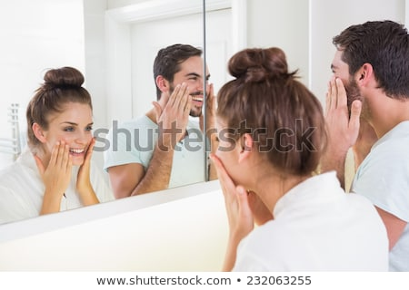 Man in bathroom applying face cream smiling Stock photo © monkey_business