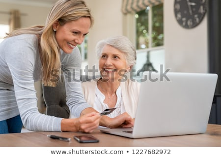 Mature woman helping elderly mother pay bills. stock photo © FreeProd