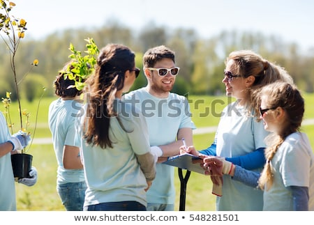 group of volunteers with clipboard in park Stock photo © dolgachov