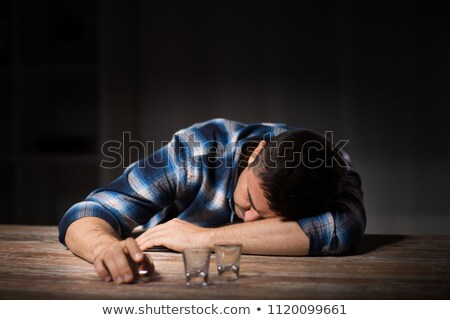 drunk man with empty glasses on table at night Stock photo © dolgachov
