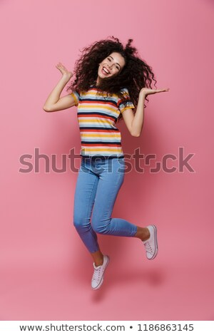 full length photo of cute woman 20s with curly hair having fun a stock photo © deandrobot