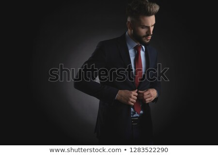 attractive businessman buttons navy suit and looks down to side Stock photo © feedough