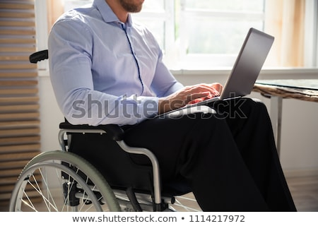 businessman sitting on wheelchair using laptop stock photo © andreypopov