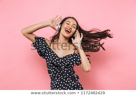 Cheerful brunette woman in dress and headphones listening music Stock photo © deandrobot