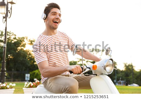 Portrait of young man 20s sitting on motorbike in city street, a Stock photo © deandrobot