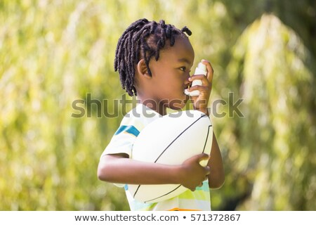 A black Boy using an asthma inhaler Foto stock © Lopolo