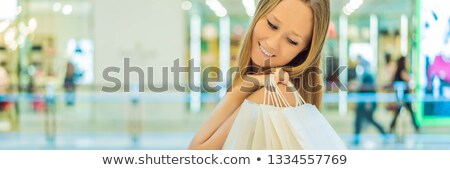 Women carrying a lot of shopping bags in blurred shopping mall BANNER, LONG FORMAT Stock photo © galitskaya