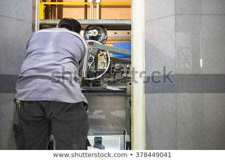 machinist worker technicians at work adjusting lift with spanner Stock photo © Lopolo