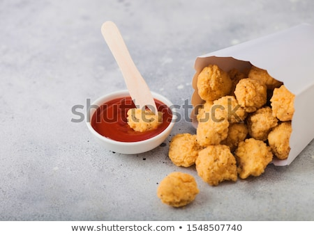 Crunchy southern chicken popcorn bites in white paper container for fast food meals with ketchup and Stock photo © DenisMArt