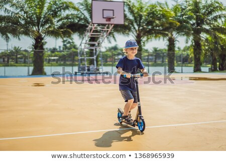 Happy child on kick scooter in on the basketball court. Kids learn to skate roller board. Little boy Stock photo © galitskaya