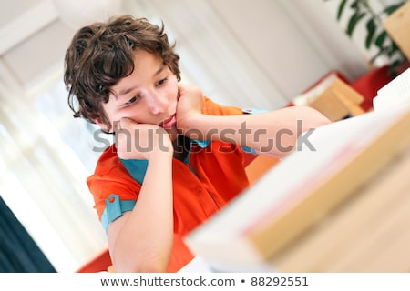 teen school boy studies hard over his book at home stock photo © lopolo