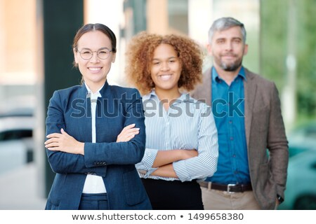 young cheerful business leader in formalwear and her team behind looking at you stock photo © pressmaster