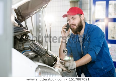 Bearded young worker of machine repair service talking to client on mobile phone Stock photo © pressmaster