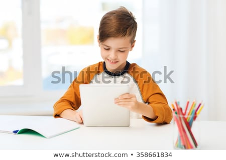 student boy with tablet pc and notebook at home Stock photo © dolgachov