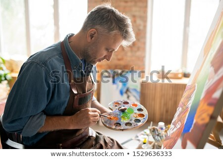Creative man in apron mixing colors on palette in front of easel in studio Stock photo © pressmaster
