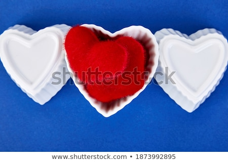 Banner of White ceramic hearts  with red plush  hearts on blue trend color background.  Stock photo © Illia